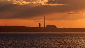 Central eléctrica en la puesta del sol Foto de archivo