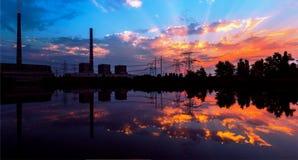 Central eléctrica en la reflexión de la oscuridad en el agua, y líneas eléctricas en la puesta del sol Imagenes de archivo