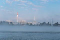 Central eléctrica industrial en la niebla antes de la salida del sol foto de archivo