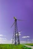 Central eléctrica - turbina de vento de encontro ao azul Fotos de Stock