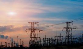 Central eléctrica y estación de alto voltaje de la transformación en la puesta del sol Imagen de archivo libre de regalías