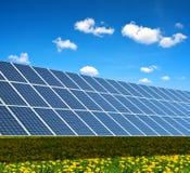 Central elétrica de energias solares no prado de florescência da mola Imagem de Stock Royalty Free