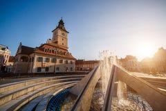 Central fyrkant för stad (Piata Sfatului) med kommunfullmäktigekorridortornet, sikt för springbrunnmorgonsoluppgång, läge Brasov, royaltyfria bilder