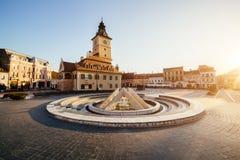 Central fyrkant för stad (Piata Sfatului) med kommunfullmäktigekorridortornet, sikt för springbrunnmorgonsoluppgång, läge Brasov, fotografering för bildbyråer