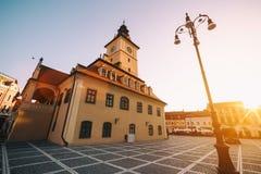 Central fyrkant för stad (Piata Sfatului) med sikten för soluppgång för morgon för kommunfullmäktigekorridortorn, läge Brasov, Tr royaltyfria bilder