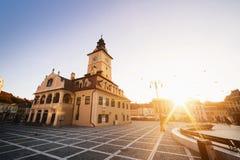 Central fyrkant för stad (Piata Sfatului) med sikten för soluppgång för morgon för kommunfullmäktigekorridortorn, läge Brasov, Tr royaltyfri bild