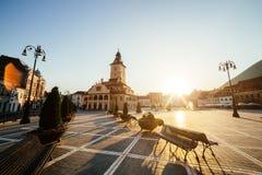 Central fyrkant för stad (Piata Sfatului) med sikten för soluppgång för morgon för kommunfullmäktigekorridortorn, läge Brasov, Tr fotografering för bildbyråer