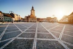 Central fyrkant för stad (Piata Sfatului) med sikten för soluppgång för morgon för kommunfullmäktigekorridortorn, läge Brasov, Tr royaltyfri fotografi