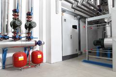 Central heating and cooling system control in a boiler room. Pumps and pipes Royalty Free Stock Photography