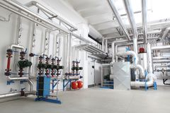 Central heating and cooling system control in a boiler room. Pumps and pipes stock photography