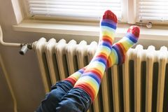 Central heating radiator and woman in striped socks
