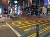 A photo taken with a slow shutter speed of pedestrians crossing at Queen`s Road Central in stock photos