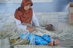 The Old woman making woven material from reeds