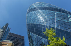CENTRAL LONDON / ENGLAND - 18.05.2014 - Sky-scraper reflections are seen in the Gherkin's windows. Stock Photo