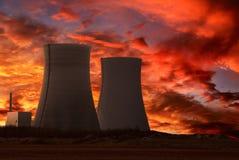 Central nuclear con un cielo rojo intenso Imagenes de archivo