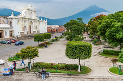 Central park & Agua volcano, Antigua, Guatemala. Antigua, Guatemala - September 7, 2009: Central park, cathedral & Agua volcano in colonial town & UNESCO World royalty free stock photo