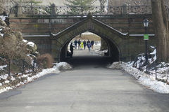 Central Park Arch. A musician plays and people walk under the Greywacke Arch, in Central Park Stock Image