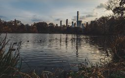Central park lake with new york skyline behind during late fall cloudy day royalty free stock photography