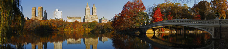Central Park panorama with Bow Bridge. Central Park (New York) Panorama in Fall as seen from the South side of the Lake and looking North West.  Visible Stock Photography