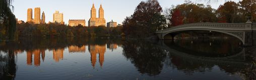 Central Park panorama with Bow Bridge. Central Park (New York) Panorama in Fall as seen from the South side of the Lake and looking North West.  Visible Royalty Free Stock Images