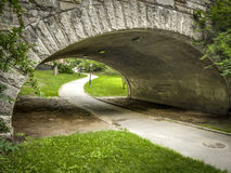 Central Park. Path going under a stone bridge in Central Park Royalty Free Stock Photos