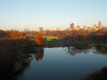 Central Park Pond with Autumn Trees and City Buildings Royalty Free Stock Images