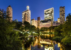 Central Park Pond and Illuminated Manhattan Skyscrapers, New York. Manhattan skyscrapers illuminated in early evening light.The buildings of Central Park South Royalty Free Stock Images