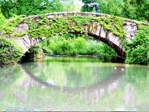 Central Park reflector de Ivy Covered Gapstow Bridge New York imagen de archivo