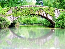 Central Park refletindo de Ivy Covered Gapstow Bridge New York imagem de stock