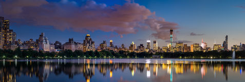 Central Park Reservoir and Midtown skyscrapers illuminated at twilight. New York City Royalty Free Stock Images