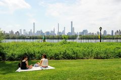 Central Park Spring. Central park in spring, New York City, USA. People sitting on the grassland in the park royalty free stock photo