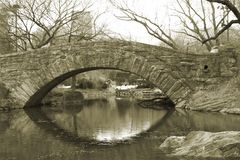 Central Park Stone Bridge. Sepia shot of a bridge in Central Park, over a pond with reflections Stock Images