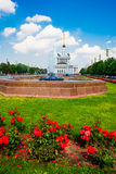 Central pavilion, exhibition center on the blue sky background. Red flowers. Fountain. ENEA,VDNH,VVC. Moscow, Russia. Stock Images