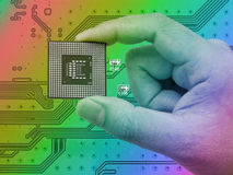 Central Processing Unit (CPU) in hand on printed green computer Royalty Free Stock Photos