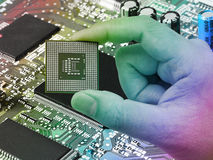 Central Processing Unit (CPU) in hand on printed green computer. Central Processing Unit CPU in hand Stock Photo