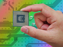 Central Processing Unit (CPU) in hand on printed green computer Stock Image