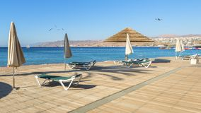 Morning at central public beach in Eilat, Israel. Central public beach with wooden floor, deck chair and parasols, concept of tourism, travel and happy vacation Royalty Free Stock Image