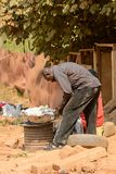 Unidentified Ghanaian man bends down to pick up food in local v. CENTRAL REGION, GHANA - Jan 17, 2017: Unidentified Ghanaian man bends down to pick up food in royalty free stock photos
