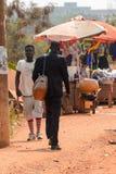 Unidentified Ghanaian man in black suit walks from behind in lo. CENTRAL REGION, GHANA - Jan 17, 2017: Unidentified Ghanaian man in black suit walks from behind stock photos