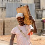 Unidentified Ghanaian man carries an old case on his shoulder i. CENTRAL REGION, GHANA - Jan 17, 2017: Unidentified Ghanaian man carries an old case on his stock photos