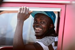 Unidentified Ghanaian man looks out of the red car's window in. CENTRAL REGION, GHANA - Jan 17, 2017: Unidentified Ghanaian man looks out of the red car's window stock photography