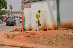 Unidentified Ghanaian man with plastic bag stands next to the w. CENTRAL REGION, GHANA - Jan 17, 2017: Unidentified Ghanaian man with plastic bag stands next to royalty free stock photos