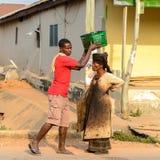 Unidentified Ghanaian man puts a basket on woman's head in loca. CENTRAL REGION, GHANA - Jan 17, 2017: Unidentified Ghanaian man puts a basket on woman's head in stock image
