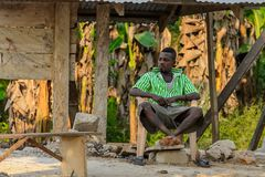 Unidentified Ghanaian man sits on plastic chair in local villag. CENTRAL REGION, GHANA - Jan 17, 2017: Unidentified Ghanaian man sits on plastic chair in local royalty free stock images