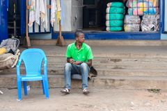 Unidentified Ghanaian man sits on stairs and listens to music i. CENTRAL REGION, GHANA - Jan 17, 2017: Unidentified Ghanaian man sits on stairs and listens to stock images