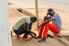 Unidentified Ghanaian man treats his friend's wound in local vi. CENTRAL REGION, GHANA - Jan 17, 2017: Unidentified Ghanaian man treats his friend's wound in stock image