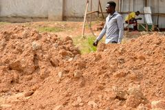 Unidentified Ghanaian man walks behind the heap of ground in lo. CENTRAL REGION, GHANA - Jan 17, 2017: Unidentified Ghanaian man walks behind the heap of ground royalty free stock photography