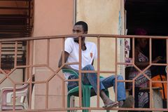 Unidentified Ghanaian man in white shirt and jeens looks away b. CENTRAL REGION, GHANA - Jan 17, 2017: Unidentified Ghanaian man in white shirt and jeens looks stock photos
