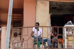 Unidentified Ghanaian man in white shirt and jeens looks away b. CENTRAL REGION, GHANA - Jan 17, 2017: Unidentified Ghanaian man in white shirt and jeens looks stock photography