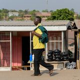 Unidentified Ghanaian man in yellow shirt with backpack walks o. CENTRAL REGION, GHANA - Jan 17, 2017: Unidentified Ghanaian man in yellow shirt with backpack royalty free stock images